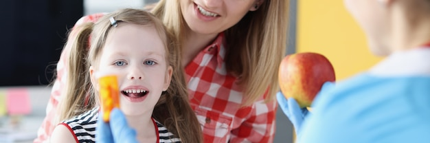 Dokter met pot capsules en rode appel voor kind en moeder in kliniek