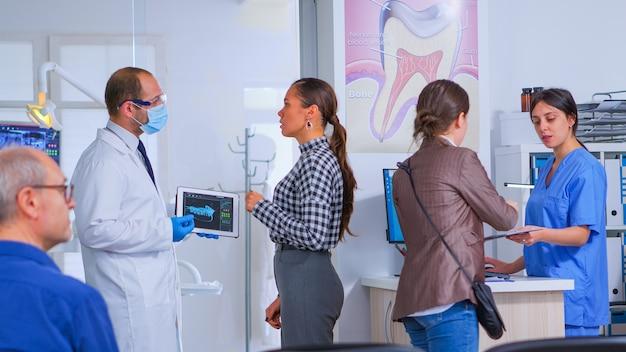 Dokter met tablet met röntgenfoto die het aan de patiënt laat zien terwijl de verpleegster de vrouw helpt bij het invullen van een tandheelkundig document. stomatoloog presenteert tandheelkundige radiografie met behulp van moderne gadget in stomatologische kliniek