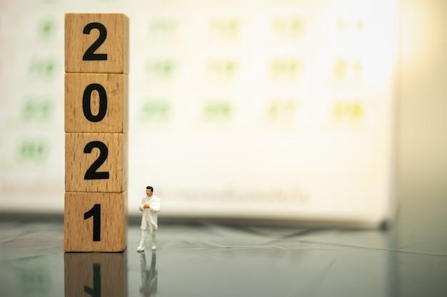 Dokter miniatuur figuur mensen lopen op de grond met stapel houten nummer 2021 blok en kalender als achtergrond.