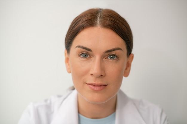 Dokter. mooie vrouw in een wit gewaad op een witte achtergrond