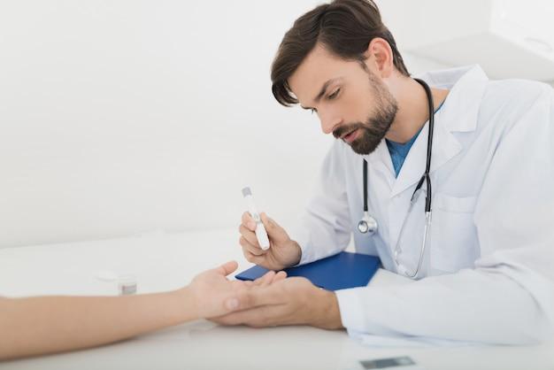 Dokter neemt een bloedmonster van de jongen om het op suiker te controleren.