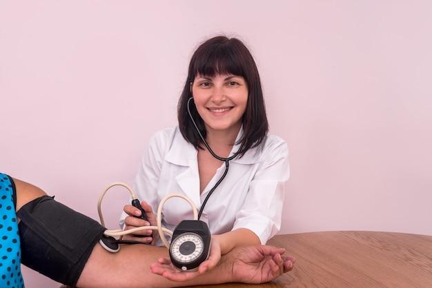 Dokter of verpleegkundige meet de bloeddruk aan de hand van de patiënt