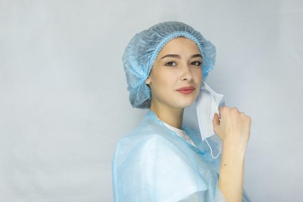 Dokter of verpleegster die haar medisch masker afdoet, portret, close-up, witte achtergrond, kopieer ruimte, meisjesverpleegster die lacht en haar medisch masker afzet
