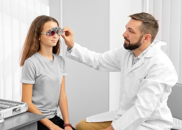 Dokter oftalmoloog die speciale oogapparatuur houdt die de ogen van tienermeisjes onderzoekt