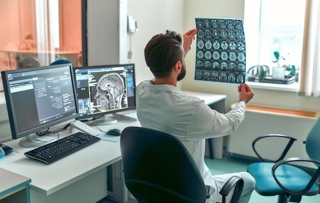 Dokter onderzoekt een mri-scan van de hersenen van een patiënt in een controlekamer