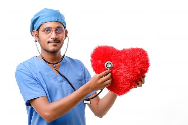 Dokter onderzoekt een rood hartvormig kussen met een stethoscoop tegen een witte achtergrond.