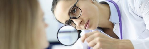 Dokter onderzoekt het gezicht van de patiënt door vergrootglas. dokter dermatoloog help concept