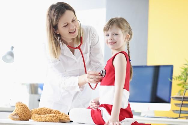 Dokter onderzoekt meisje met stethoscoop kinderen gezondheidszorg concept