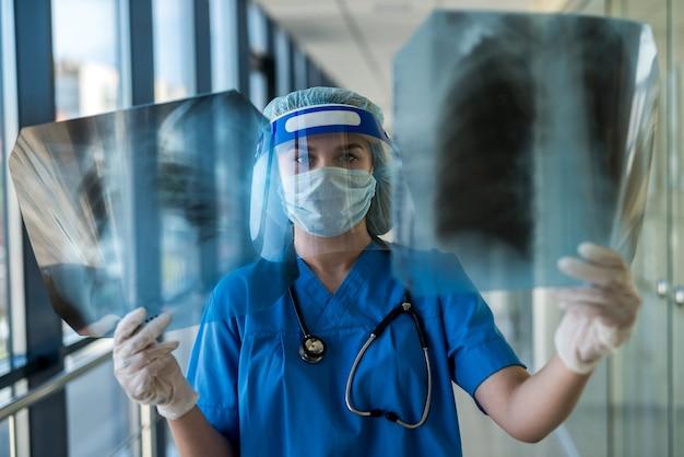 Dokter onderzoekt röntgenfoto van longen in gezichtsscherm en masker om longontsteking te bepalen veroorzaakt door een nieuw virus covid19