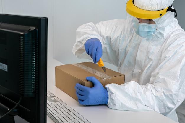 Dokter op beschermend pak en plastic gelaatsscherm opent een doos met gezichtsmaskers tijdens covid 19. vervuilde post