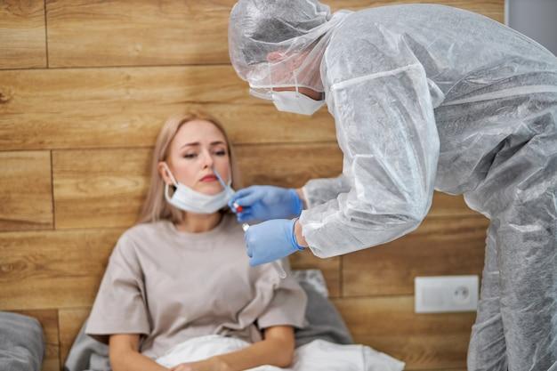 Dokter op bezoek bij ongezonde zieke vrouw thuis, coronavirus covid-19 testen. arts raadpleegt patiënt zittend op bed. patiëntenzorg. diagnostiek.