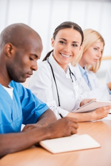 Dokter op de vergadering. mooie jonge vrouwelijke arts die lacht terwijl ze samen met haar collega's op de meeting zit