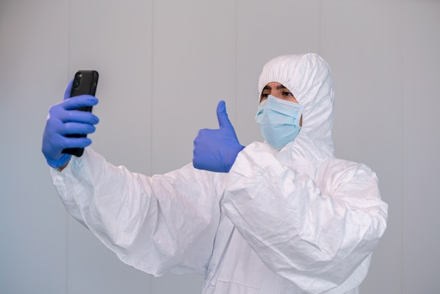 Dokter op pbm en een duim omhoog gebaren tijdens het raadplegen van mobiele applicatie op smartphone tijdens een pandemie van covid 19. telegeneeskunde concept