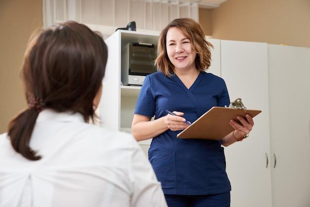 Dokter praat met jonge vrouwelijke patiënt en maakt aantekeningen terwijl hij in zijn kantoor staat
