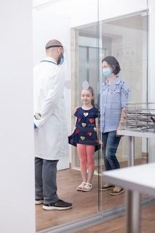 Dokter praat met patiënten in het ziekenhuis die tijdens consultatie gezichtsmasker dragen tegen wereldwijde pandemie
