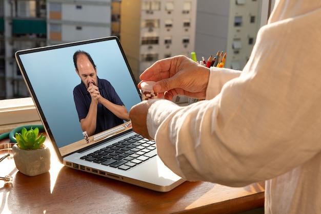 Dokter praat met zijn patiënt via telegeneeskunde tijdens de coronaviruspandemie bij zijn voor-tot-raam-kantoor. de patiënt is wanhopig op zoek naar covid-19
