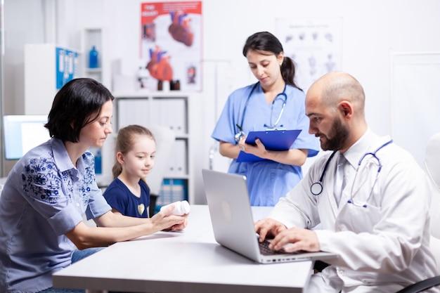 Dokter schrijft behandeling op laptop tijdens consultatie van kind en moeder in ziekenhuiskantoor. medisch specialist in de geneeskunde die medische zorg onderzoekt.