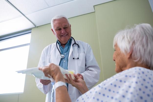Dokter serveert ontbijt en medicijnen aan senior patiënt