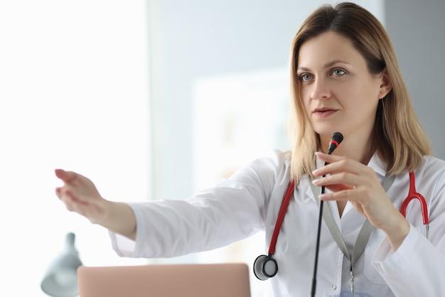 Dokter spreken in de microfoon op conferentie en zwaait met zijn hand