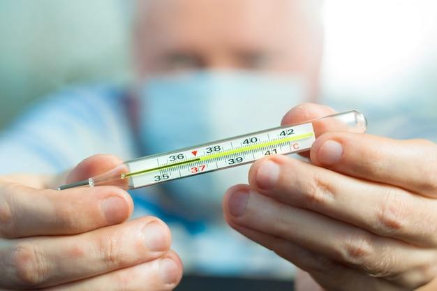 Dokter toont de thermometer die de koorts markeert