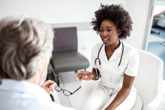 Dokter troost haar volwassen patiënt in de wachtkamer in de medische kliniek.