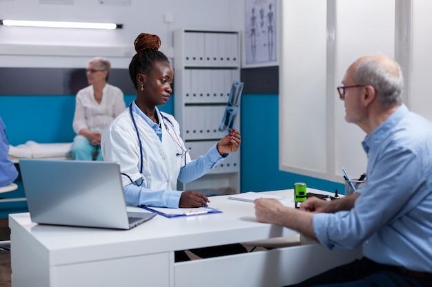 Dokter van afro-amerikaanse etniciteit die röntgenfoto vasthoudt voor oude patiënt