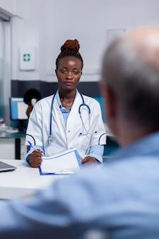 Dokter van afro-amerikaanse etniciteit in gesprek met oudere man