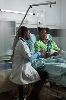 Dokter van afro-amerikaanse etniciteit met radiografie in ziekenhuisafdeling. afro-vrouw die naar röntgenfoto's kijkt met jonge patiënt voor herstel van de behandeling. zwart meisje zit in bed en praat met medic