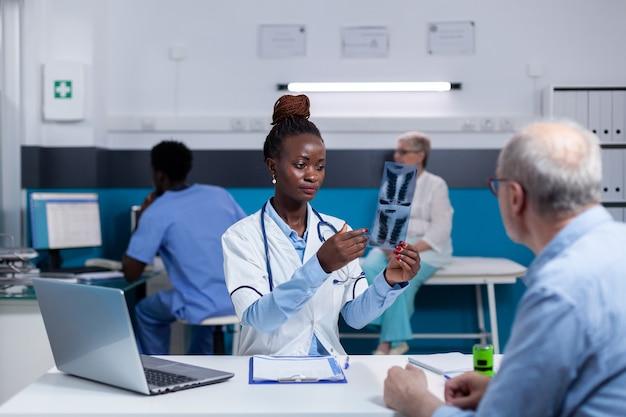 Dokter van afro-amerikaanse etniciteit met röntgenfoto voor oude patiënt