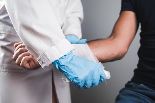 Dokter verbindt de hand van een man.