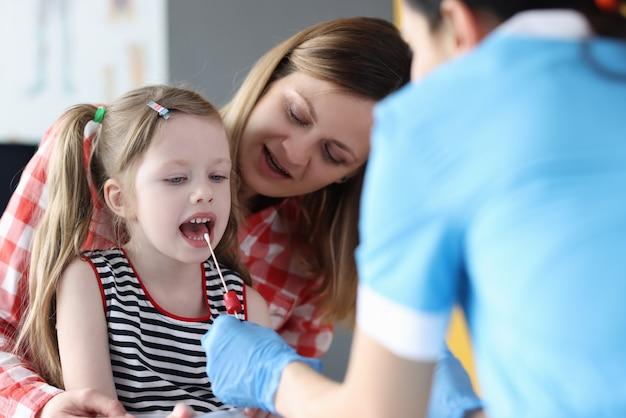 Dokter verzamelt biologisch materiaal uit speeksel van kinderen