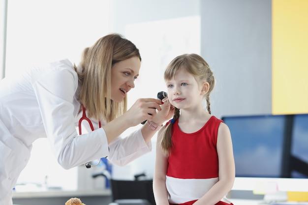 Dokter voert medisch onderzoek uit van oor van klein meisje