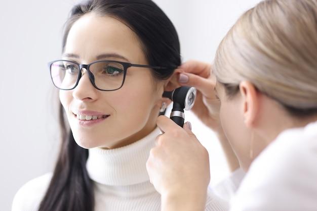 Dokter voert onderzoeken van het oorgebied uit voor de vrouw