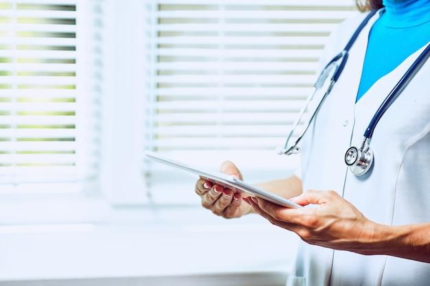 Dokter werkt aan een digitale tablet met kopieerruimte