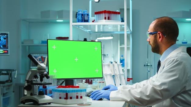 Dokter werkt op computer met groen scherm na verloop van tijd zittend in modern uitgerust lab. team van microbiologen die vaccinonderzoek doen en schrijven op apparaat met chroma key, geïsoleerd, mockup-display.