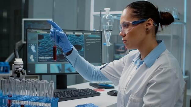 Dokter werkzaam in wetenschappelijk laboratorium met reageerbuizen