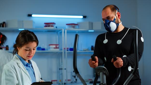 Dokter wetenschap typen op tablet tijdens het meten van het uithoudingsvermogen van sporters met behulp van lichaamssensoren en masker monitoring hartritme. man loopt op crosstrainer in sportlab, specialisten houden toezicht op oefening