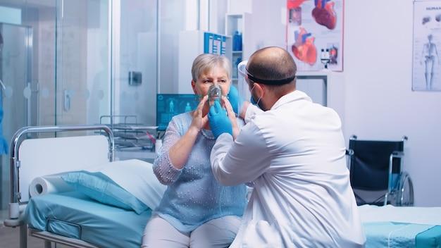 Dokter zet een zuurstofmasker op oude gepensioneerde senior vrouw tijdens de uitbraak van covid-19 coronavirus in een modern privéziekenhuis of -kliniek. bestrijding van infectie en ziekte geneeskunde en quarantaine