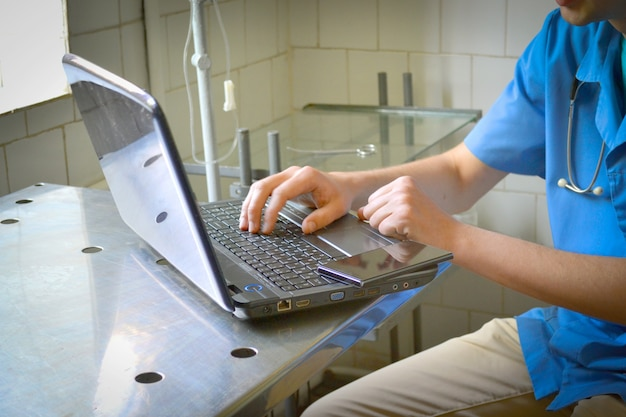 Dokter zit aan bureau en typt op laptop