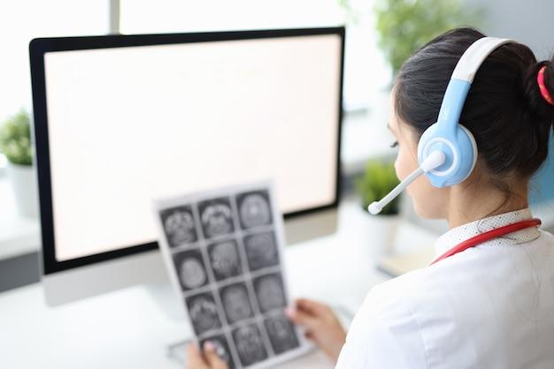 Dokter zittend in medisch kantoor in hoofdtelefoons met microfoon