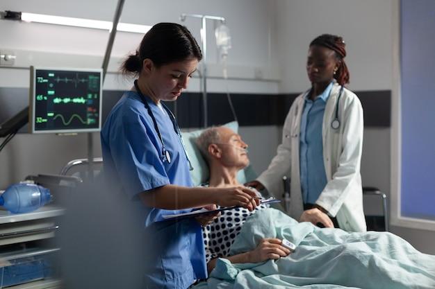 Dokterassistent maakt aantekeningen op cliboard terwijl afrikaanse arts senior patiënt geruststelt