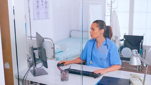 Dokterassistent typen op de computer met een monitor achter een glazen wand op kantoor. arts in de geneeskunde uniforme schrijflijst van geraadpleegde, gediagnosticeerde patiënten, die onderzoek doen.