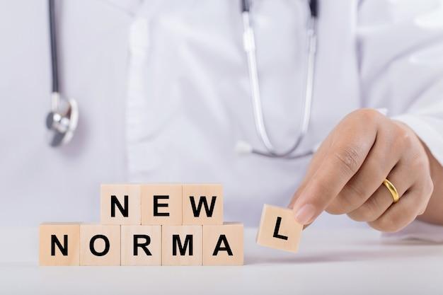 Dokterhand schikken van houten kubussen met nieuw normaal woord. nieuw normaal na covid-19 pandemie met sociaal afstands-, milieu- en gezondheidsconcept