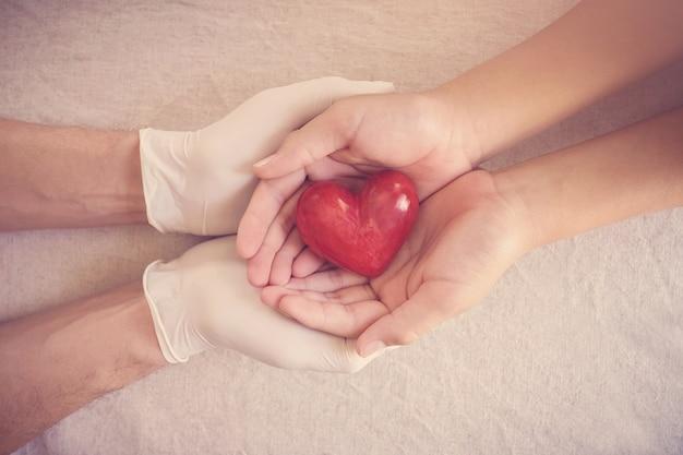 Dokterhanden met handschoenen die kindhanden, rood hart, ziektekostenverzekering, schenkingconcept houden