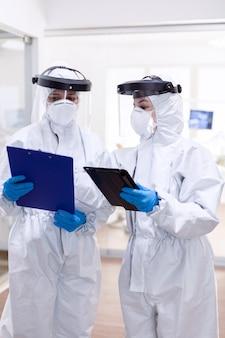 Dokterpersoneel in pbm-pak tijdens wereldwijde pandemie met covid-19. medische collega's die professionele uitrusting dragen tegen infectie met coronavirus als veiligheidsmaatregel.