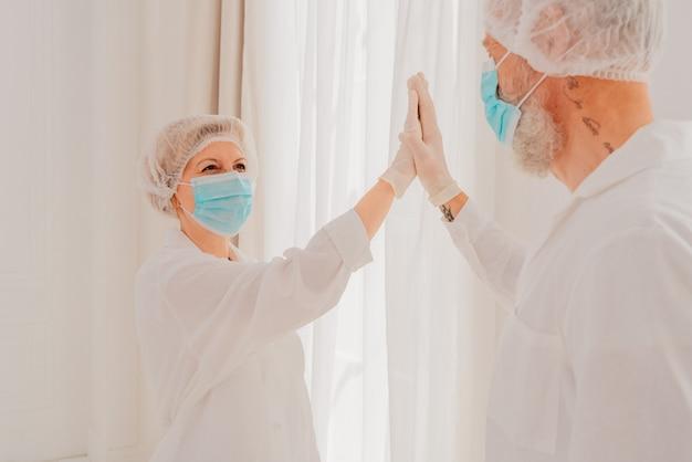 Dokters met masker en gezichtsbeschermer geven elkaar een handje