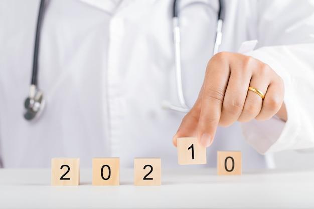 Doktershand met houten blokken voor 2021. nieuwjaar en gezondheidsconcept.
