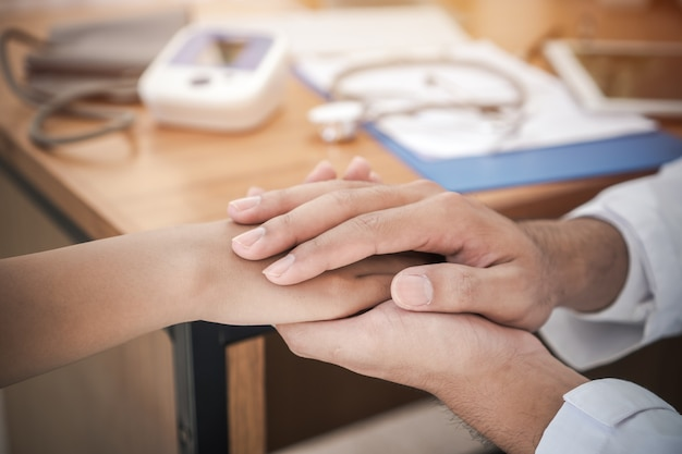 Doktershanden houden vrouwelijke patiëntenhand vast voor geruststelling met vriendelijke aanmoediging empathie voor ondersteuning