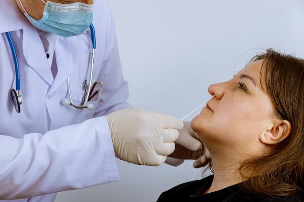 Doktersmedewerker neemt een uitstrijkje een coronavirus covid-19 test een neusmonster voor medisch onderzoek voor in vrouwelijke test