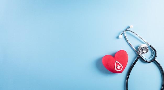 Dokterstethoscoop en een handgemaakt rood hart met een teken of symbool van bloeddonatie